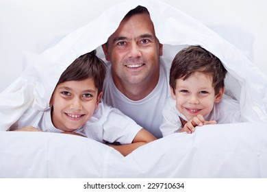 Father and his sons spending some lazy time together having fun