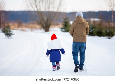 father and his toddler daughter walking together at snowy park, winter day