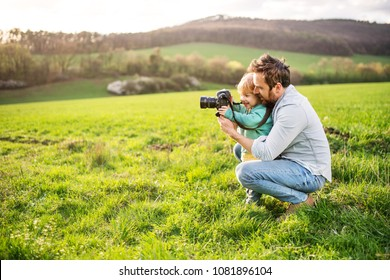 A father and his toddler son with a camera outside in spring nature.