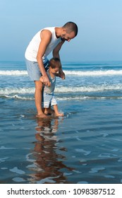 The father and his toddler son on the beach in the morning. They standing in the water and father holds son and smilling. The father teaches his son how to go.