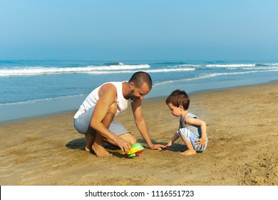 The father and his toddler son on the beach in the morning. Father plays toy plane with his son. The father teaches his son how to go.