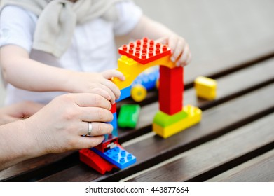 Father with his toddler son playing with colorful plastic blocks