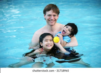 Father and his two children enjoying the pool