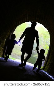 a father and his two children, a little boy and a baby are holding hands, and flashlights and walking down a trail into a dark stone tunnel