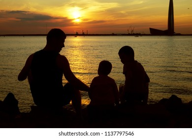 Father with his two sons on sunset beach, silhouette photo
