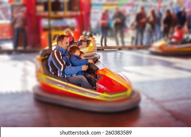 Father and his two sons,l having a ride in the bumper car at the amusement park