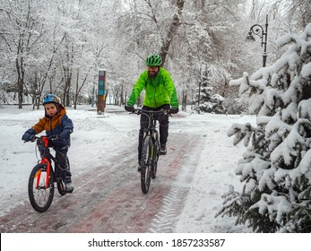 A father and his young son spend an active weekend in the winter on bicycles. Man and his son ride bicycles on the bike path in the winter park