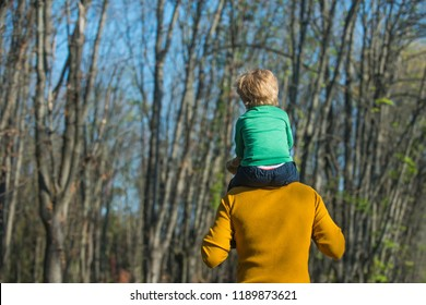 Father hold little son on shoulders giving child piggyback in park. Piggyback ride. Take me to the top.