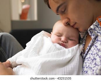Father holding baby. Both are sleeping. Horizontally framed shot.