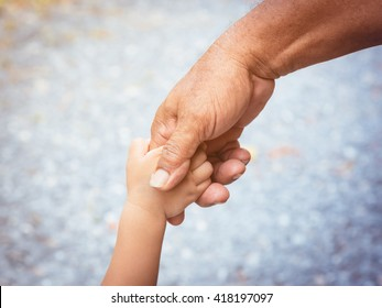 Father holding baby hand finger and color tone effect