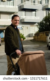 father holding brown pushchair in front of building - faterhood