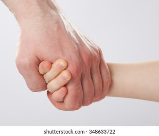 Father holding child's hand, closeup shot on grey background