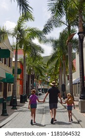 Father holding daughters hands while walking down Front Street, Philipsburg, St Maarten
