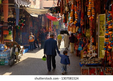 Father holding hand of son while strolling in the souk of Marrakech, Morocco - November 12, 2010