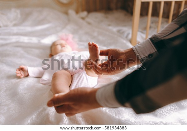 father holding hands baby fingers on a white blanket
