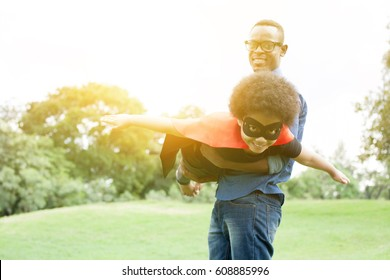 Father holding and helping flying super hero kid together in happiness