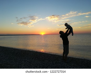 Father holding his baby up during sunrise