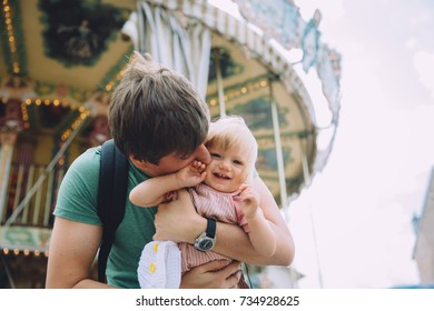 Father holding his baby girl near merry-go-round carousel