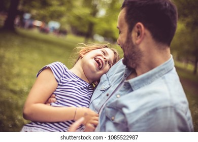 Father holding his daughter and looking at her. Day at park.