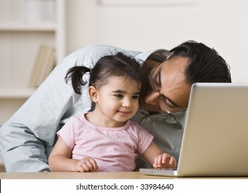 A father is holding his daughter on his lap and helping her play on the computer.  He is looking at his daughter and she is looking at the screen.  Square framed shot.