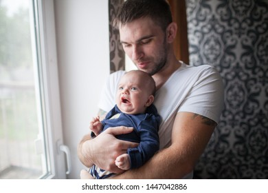 Father holding his little baby boy at home