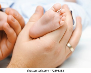 Father holding his newbon baby's feet