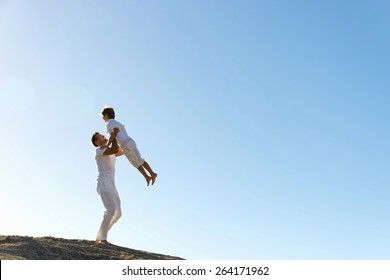Father  holding his son in his arms on top of a hill.