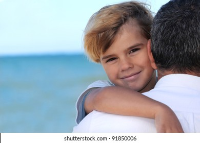 father holding his son on the beach
