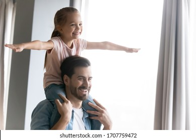 Father holding little cute daughter on shoulders having fun together at home, small adorable kid girl stretched arms imagines herself like a plane flying, funny activity with children indoors concept