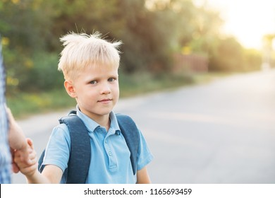 Father holding little son's hand. Little schoolboy with backpack looking at the camera and going to school. Back to school concept.
