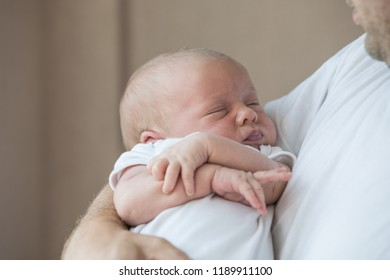 Father holding newborn baby son at the day time. Concept of happy family.