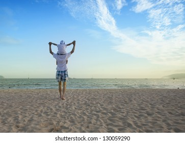 Father holding son on his shoulders at the beach with blue sky