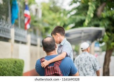 Father holding son while walking on the street when he tried