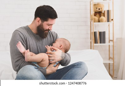 Father holding and soothing crying little newborn baby in his arms. Hungry kid looking for mothers breast, copy space