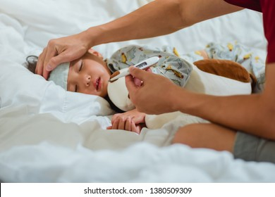 father holding thermometer foreground of sick little girl in bedroom at night time for monitor high fever with thermometer for ,Kid had high fever and tepid sponging to bring the temperature down