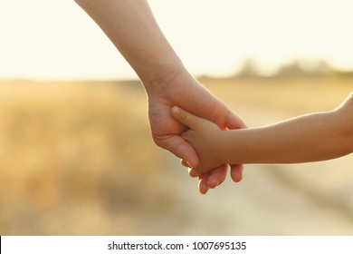 Father holds daughter by the hand. Shooting close-up. In the background, out of focus is a country road. Support on the way.