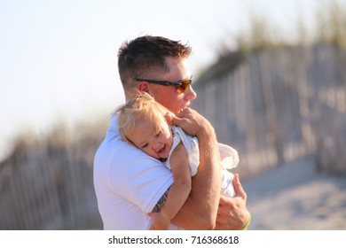 A father holds his baby daughter on the beach
