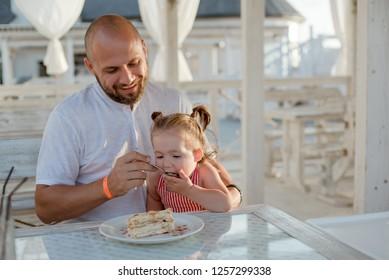 A father holds his little daughter in his arms while sitting at a table in a summer cafe by the sea, carefully feeding her with a spoon.
