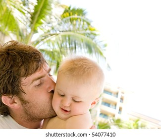 A father holds and kisses his baby son, with a muted tropical setting in the background and white space for copy.