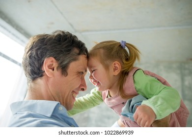 Father holds the little daughter on hands. A touching little girl looks at her father with delight. The man looks happy.