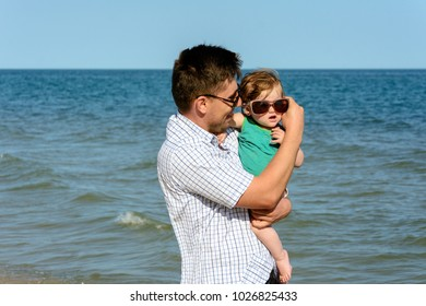 Father holds a little daughter on his shoulders in sunglasses