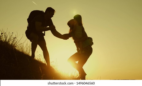 father holds out his hand helping children climb mountain. Family of tourists with kids traveling at sunset. dad, children and mom with backpacks travel climb mountain in sun. tourist teamwork