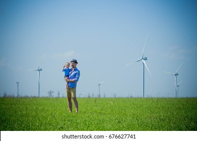 Father holds son in his arms on an eco-friendly green field with alternative sources of energy wind generators