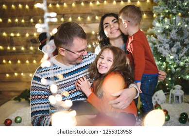 father hugging happy daughter in christmas lights