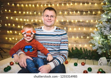 father hugging son in glasses with snowman in christams lights