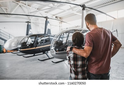 Father hugging son while watching at rotorcraft. They turning back to camera