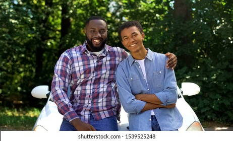 Father hugging teenage male child smiling on camera standing auto background