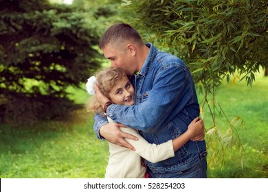 Father hugs daughter teen summer outdoors, happy family resting in the Park. The concept of traditional family values
