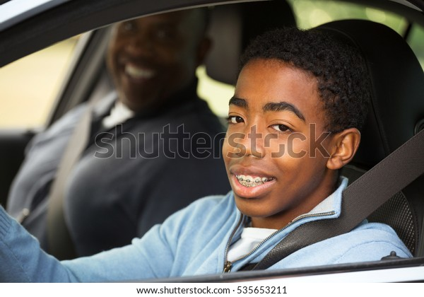 Father instructing his son on driving.
