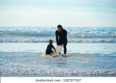 Father or instructor teaching small kid how to surf in the sea. Travel and sports with children concept. Surfing lesson for kids. California, San Diego, La Jolla Beach, USA. 01/08/2019